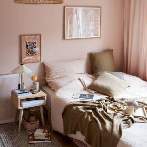Bett mit rosa Bettwäsche und rosa Wandfarbe
